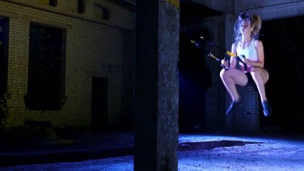 sportovní, sexy žena provádí cvičení s fitness systém trx, Trx popruhy suspenze. V noci na lehký kouř, mlha, ve světle různobarevné reflektory v opuštěné budově