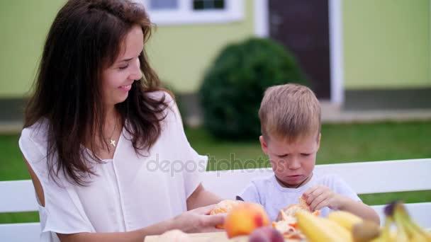 léto v zahradě. Máma a čtyři rok starý syn vyčistit z kůry pomeranče. chtějí udělat čerstvý džus