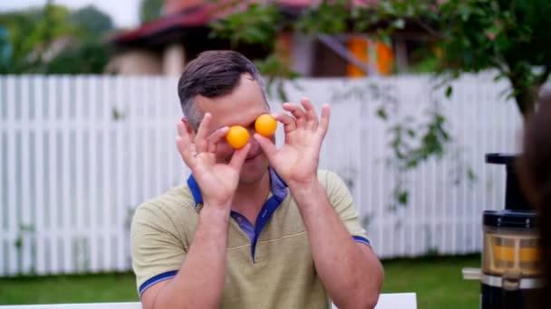léto v zahradě. Muž, otec, baví se svou rodinou venku, kroucení, použití mandarinky na oči. Rodinná dovolená, oběd na povaze, na nádvoří