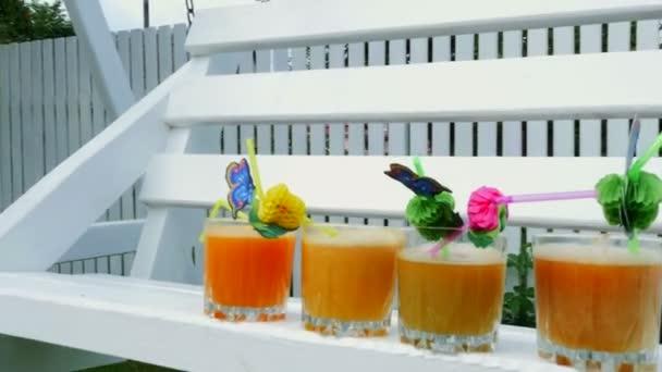 Nahaufnahme, auf weißer Holzschaukel, im Garten, im Sommer stehen 4 Gläser mit frisch gepressten Orangen- und Pfirsichsäften, dekoriert mit Strohhalmen für Cocktails