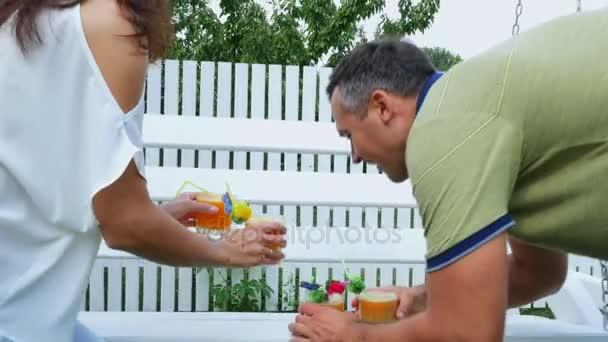 nyári kert, szülők, anya és apa, carry frissen facsart gyümölcslé a gyermekek kezelésére. A család saját szabadidejüket együtt tölt.