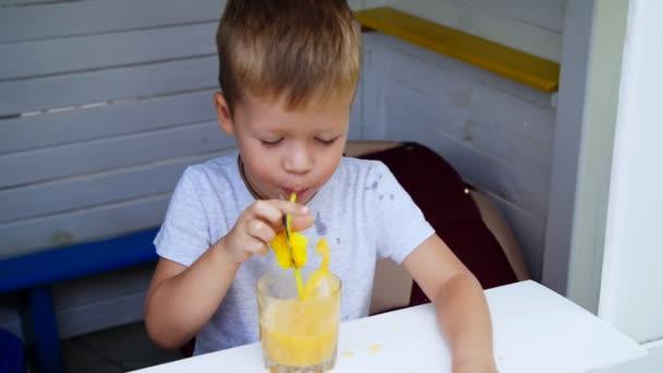 portrét, čtyři rok starý chlapec kazí s džusem, umožňuje bubliny do šťávy brčkem, dělá cibule, šplouchání. je šťastná, směje se, jásá.