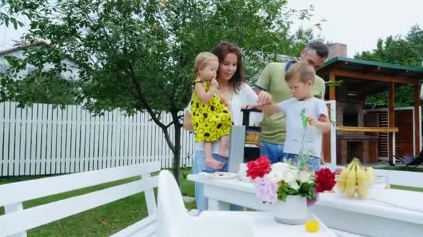 Happy rodinkou, maminku, tatínka, syna čtyři roky starý a jeden rok stará dcera vyrobit čerstvou šťávu z hroznů. V létě se v zahradě. rodina tráví svůj volný čas společně