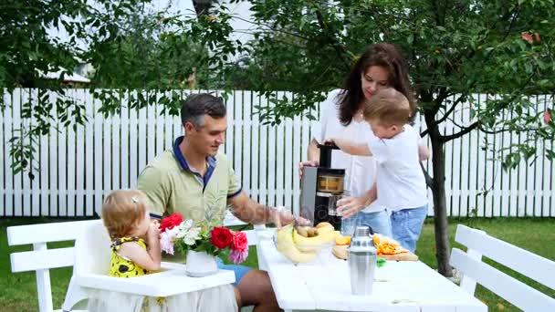 Happy rodinkou, maminku, tatínka, syna čtyři roky starý a jeden rok stará dcera, aby čerstvé ovocné šťávy. V létě se v zahradě. Rodina tráví společně svůj volný čas.