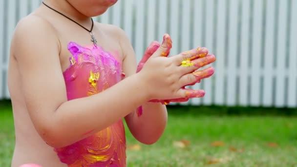 malé dítě, čtyři rok starý chlapec, hraní, Malování prstem barvy, zdobení, v zahradě, seděla na dece na trávě, trávníku, v létě. HES baví