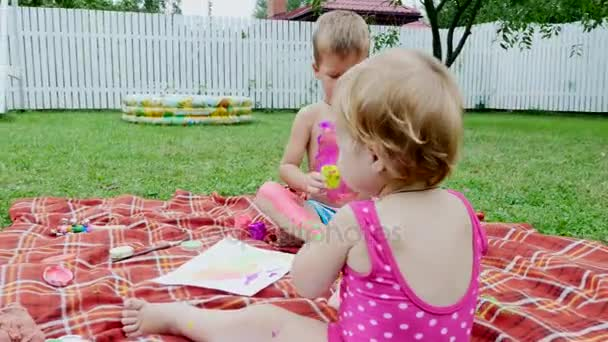 bambini piccoli, un quattro-anno-vecchio ragazzo e una ragazza di one-year-old, fratello e sorella, giocare insieme, dipingere con pitture a dito, nel giardino, seduta su una coperta, su erba, Prato, in estate