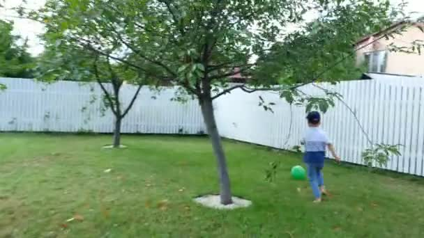 táta s čtyři rok starý syn hrát míč, fotbal, na dvoře na zeleném trávníku, v létě