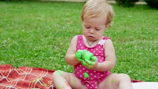 un bambino, una ragazza di one-year-old giocando, dipinto con pitture a dito, se stessa, decorazione in giardino, seduti su una coperta, copriletto, sullerba, Prato, in estate. shes divertendosi