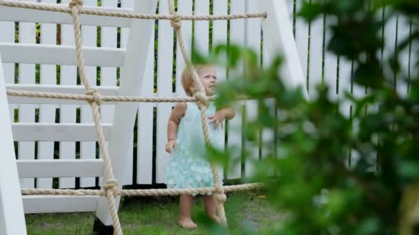l\'été, dans le jardin, enfant, une fille de 1 ans va monter l ...