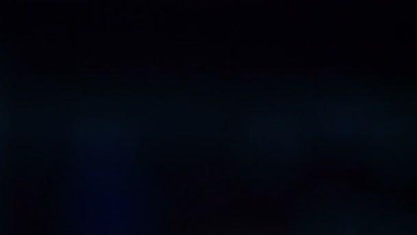 Ve tmě blikají světla, reflektory, světlomety a svítilny. Barevná hudba, disco. Noční.