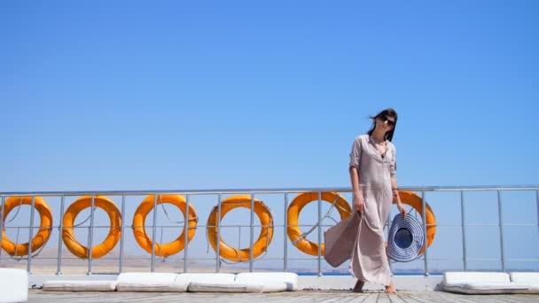 Sommer, Meer, schöne junge brünette Frau, in einem langen Kleid und Sonnenbrille, steht auf dem Deck einer Fähre, Schiff und genießt den Rest, die Schönheit des Meeres. An Bord hängen viele Rettungsringe.