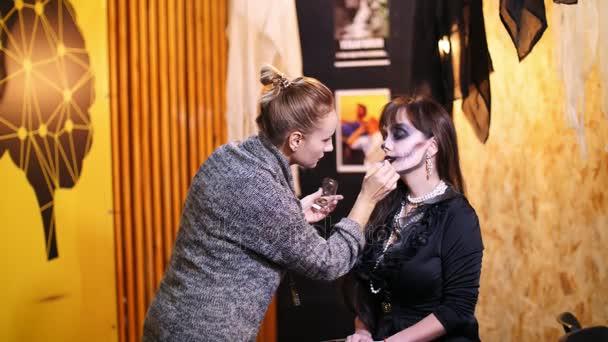 Halloween-Party, Make-up-Artist zieht eine schreckliche Make-up auf dem Gesicht eine Brünette Frau für eine Halloween-Party. im Hintergrund sieht man die Landschaft im Stil von Halloween