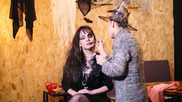 halloween party, Make-up-Artist zeichnet eine schreckliche Make-up auf das Gesicht einer brünetten Frau für eine halloween party. im Hintergrund ist die Szenerie im Stil von Halloween zu sehen