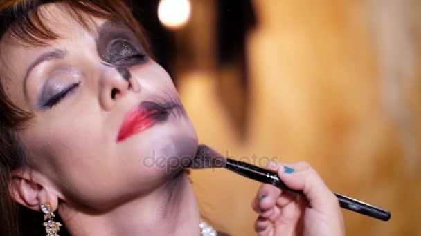 halloween party, close-up, make-up artist zeichnet ein schreckliches Make-up auf das Gesicht einer brünetten Frau für eine halloween party. die Szenerie im Stil von halloween wird gesehen