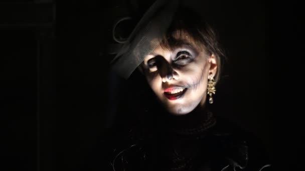 Halloween-Party, Nacht, Porträt einer Frau in der Dämmerung in den Strahlen des Lichtes erschreckend. Frau mit einem schrecklichen Make-up in einem schwarzen Hexenkostüm