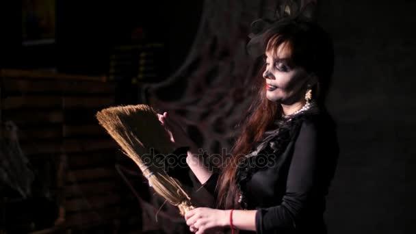 Halloween-Party, Nacht, Porträt einer Frau in der Dämmerung in den Strahlen des Lichtes erschreckend. Frau mit einem schrecklichen Make-up in einem schwarzen Hexenkostüm. Sie hält einen Besen mit einer Fledermaus