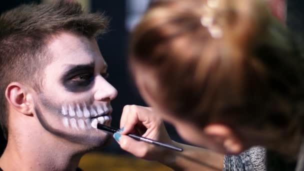 Halloween Party, close-up, Make-up-Artist zieht eine schreckliche Make-up auf dem Gesicht eines Mannes für eine Halloween-Party. im Hintergrund sieht man die Landschaft im Stil von Halloween