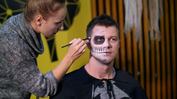 Halloween-Party, Maskenbildner zeichnet ein schreckliches Make-up auf das Gesicht eines Mannes für eine Halloween-Party. im Hintergrund ist die Szenerie im Stil von Halloween zu sehen