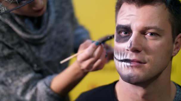 Halloween-Party, Nahaufnahme, Make-up-Artist zeichnet eine schreckliche Make-up auf das Gesicht eines Mannes für eine Halloween-Party. Im Hintergrund ist die Szenerie im Stil von Halloween zu sehen