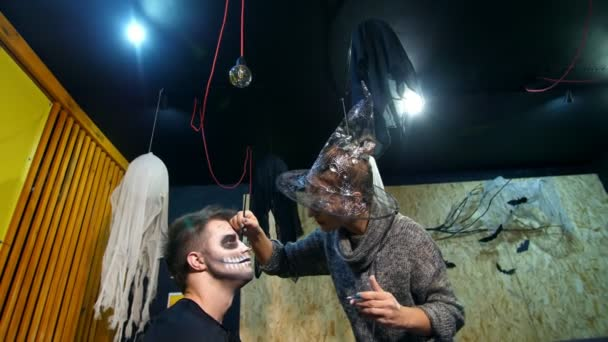 Halloween-Party, Make-up-Artist zieht eine schreckliche Make-up auf dem Gesicht eines Mannes für eine Halloween-Party. im Hintergrund sieht man die Landschaft im Stil von Halloween