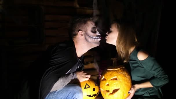 date in style of Halloween party, night, twilight, in the rays of light, guy with a girl dressed in costumes and with a terrible makeup are holding two large Halloween pumpkins, kissing