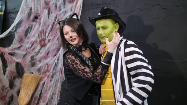 Halloween-Party, Fotosession, junge Leute in gruseligen Kostümen und schrecklich geschminkt. sie amüsieren sich, im Hintergrund ist die Halloween-Szenerie zu sehen