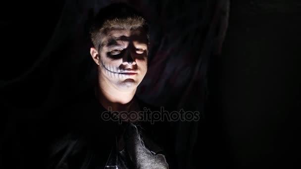 Halloween-Party, Nacht, Porträt eines Mannes in der Dämmerung in den Strahlen des Lichtes beängstigend. Mann mit einem schrecklichen Make-up in einem schwarzen Hexenkostüm
