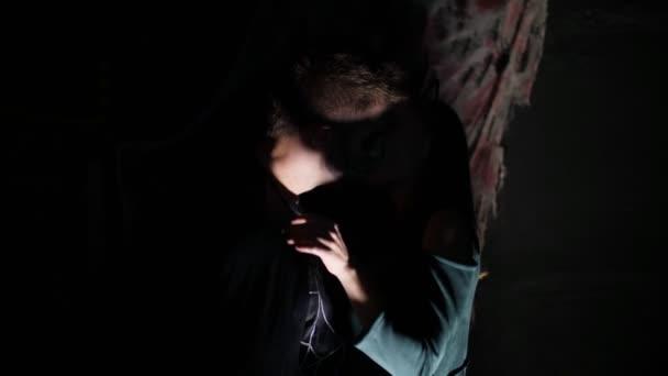 Festa di Halloween, notte, spaventoso uomo al crepuscolo, nei raggi di luce, con un terribile make-up in un costume da strega nera. demone bacia la ragazza. il bacio di werewolfs