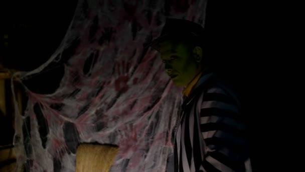 Halloween-Party, Nacht, Dämmerung, in den Strahlen des Lichtes, ein Mann mit einem schrecklichen Make-up mit einer grünen Fläche und einem Hut lacht unheimlich, Angst, hinter der Rückwand ist ein Spinnennetz.