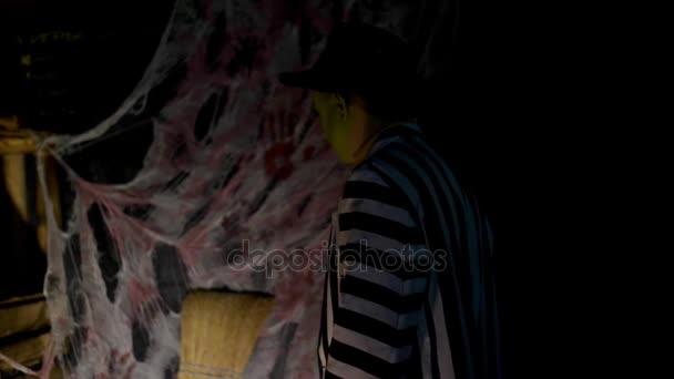 Halloween-Party, Nacht, Dämmerung, in den Lichtstrahlen zeigt ein schrecklich geschminkter Mann mit grünem Gesicht und Hut Angst und läuft davon. Hinter dem Hintergrund steckt ein Spinnennetz.