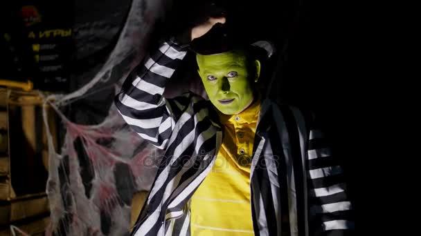 Halloween-Party, Nacht, Dämmerung, in den Lichtstrahlen hebt ein schrecklich geschminkter Mann mit grünem Gesicht und Hut seinen Hut, lüftet seine Zunge, lacht unheimlich und rennt davon.