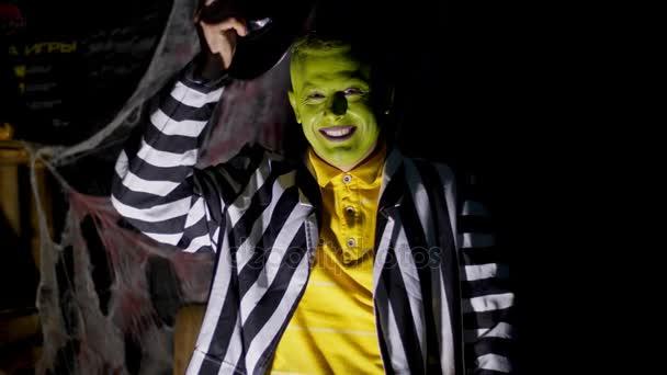 Halloween-Party, Nacht, Dämmerung, in den Lichtstrahlen hebt ein schrecklich geschminkter Mann mit grünem Gesicht seinen Hut, lacht unheimlich und läuft davon. Hinter dem Hintergrund steckt ein Spinnennetz.