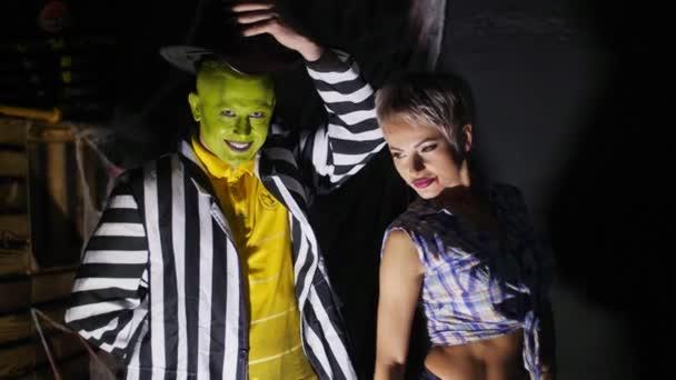 Halloween-Party, Nacht, in den Strahlen des Lichts, ein schrecklich geschminkter Mann mit grünem Gesicht und Hut, der unheimlich lacht, das Mädchen im Schulmädchenanzug belästigt und ihr in den Arsch schlägt,