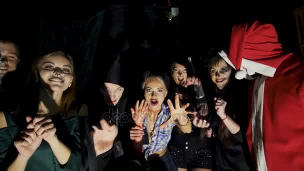 Halloween-Party, Nacht, Dämmerung, in den Strahlen des Lichts erschrecken junge Leute die Zuschauer, alle sind zu Halloween in gruselige Kostüme gekleidet.