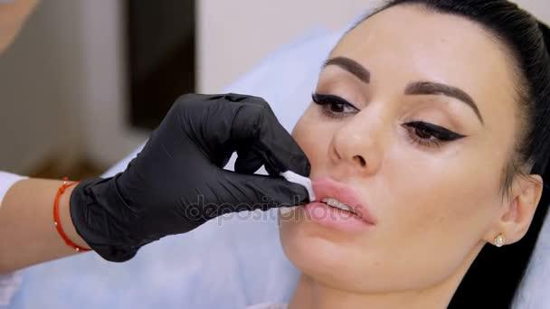 zdravotní úřad, lékař v černé sterilní rukavice, injekce kyseliny hyaluronové do pacienta rty. Postup pro zvýšení objemu rtů, Korekce tvaru rtů