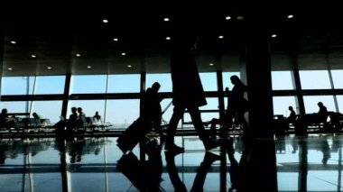 at the airport, in the waiting room, against the background of the window overlooking the planes and the runway, people silhouettes walk, they hurry on their flights