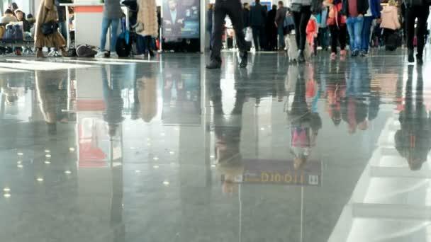 Flughafen, Warteraum, auf dem Fliesenboden spiegeln sich Figuren von Menschen. Menschen eilen hin und her.