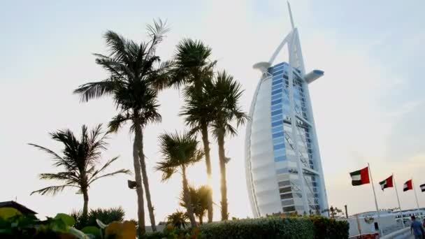 Dubaj, Spojené arabské emiráty, SAE - 20. listopadu 2017: Hotel Burj al Arab, při západu slunce, jsou vidět palmy, příznaky se rozvíjejí ve větru