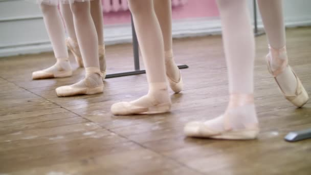 in ballet hall, Young ballerinas perform battement tendue back in pointe shoes, close-up