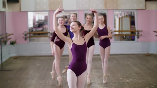 portrait of a young girl ballet dancer in a lilac ballet leotard, smiling, sending an air kiss, gracefully performing a ballet figure.