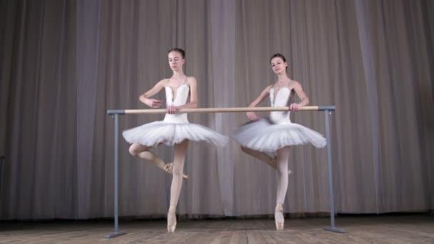 Ballettprobe, im alten Theatersaal. junge Ballerinen in weißen Ballettröcken, Tutus, sind beim Ballett engagiert, führen elegant eine bestimmte Ballettübung aus, passen, attidude, stehen in der Nähe von Barre