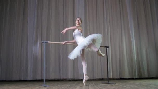 Ballettprobe, im alten Theatersaal. junge Ballerina im weißen Ballettrock, Tutu, engagiert sich beim Ballett, führt elegant eine bestimmte Ballettübung aus, Haltung allonge, steht in der Nähe von Barre