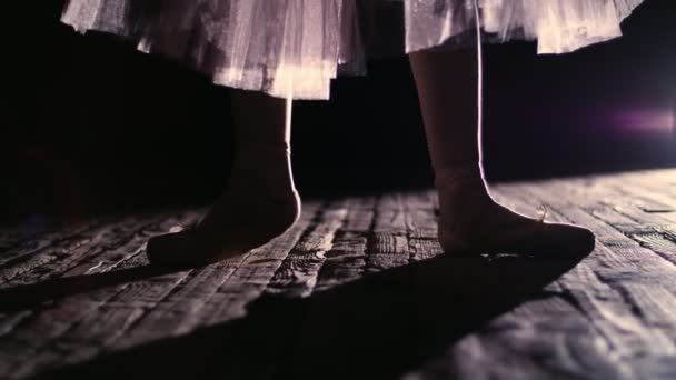 close up, in rays of spotlight, on the stage of the old theater hall. ballerina in white ballet skirt, raises on toes in pointe shoes, performs elegantly a certain ballet exercise, pointe