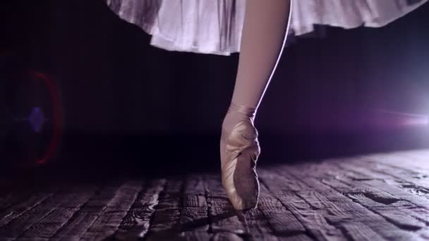 close up, in rays of spotlight, on stage of old theater hall. ballerina in white ballet skirt, rotates on toe in pointe shoe, performs elegantly a certain ballet exercise, tour,pointe