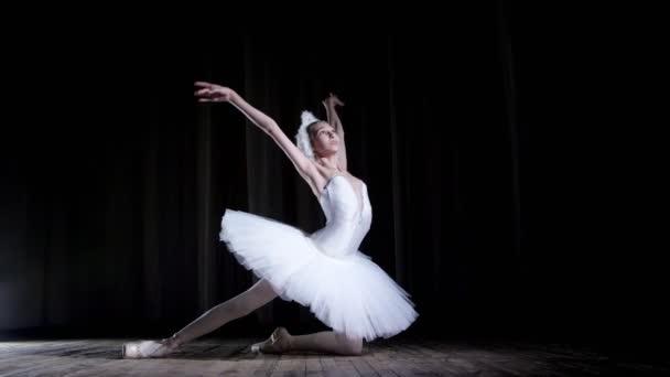 im Scheinwerferlicht auf der Bühne des alten Theatersaals. junge Ballerina im Anzug aus weißem Schwan und Spitzenschuhen, tanzt elegant bestimmte Ballettbewegungen, Schwanensee