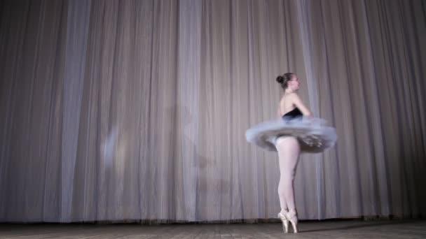 Ballettprobe, auf der Bühne des alten Theatersaals. junge Ballerina in weißem Balletttutu und Spitzenschuhen, tanzt elegant bestimmte Ballettbewegungen, Tourketten