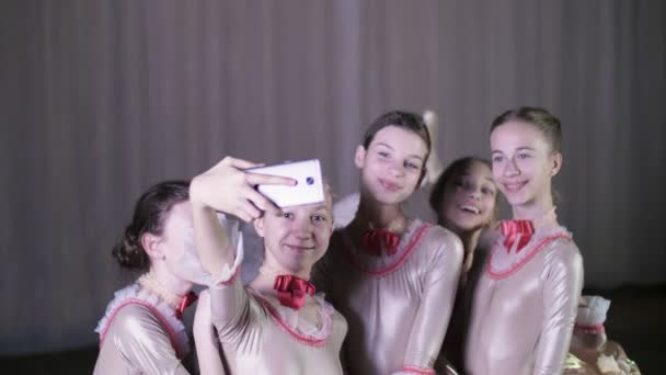 junge Ballerinas machen Selfies während einer Pause in der Ballettprobe auf der Bühne des alten Theatersaals.