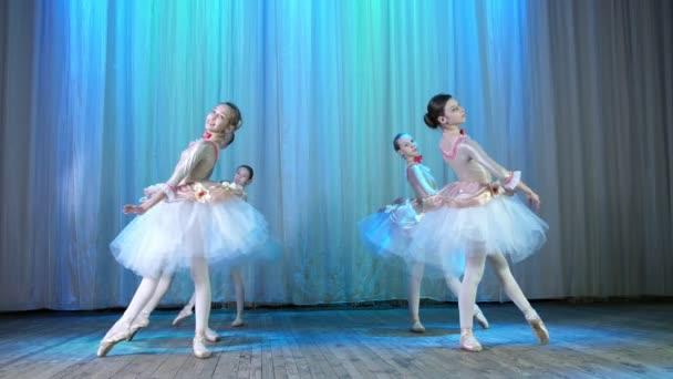 balet zkouška na jevišti staré divadelní sál. Mladí baleríny v elegantní šaty a pointe boty, taneční elegantně určitých baletní pohyby, pass, arabeska, tempiplie