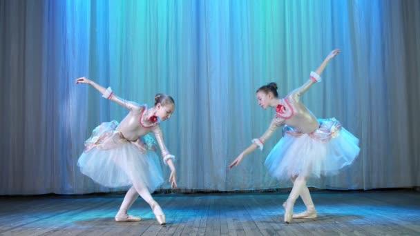 Ballettprobe, auf der Bühne des alten Theatersaals. junge Ballerinen in eleganten Kleidern und Spitzenschuhen, tanzen elegant bestimmte Ballettbewegungen, Pass, szenische Verbeugung