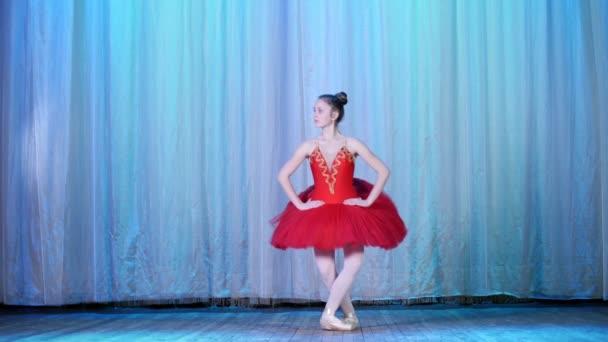 Ballettprobe, auf der Bühne des alten Theatersaals. junge Ballerina in rotem Balletttutu und Spitzenschuhen, tanzt elegant bestimmte Ballettbewegungen, Weichei einfach